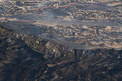 July 5, 2018 - Leilani Estates, Hawaii, U.S. - Lava, from small overflows, cools and congeals along the banks of the lava channel to build lava levees. The levees also build up as moving lava pushes cooled crust over the edge. This image of the lava levee and perched lava channel were taken during the morning helicopter overflight of the lower East Rift Zone, in the vicinity of Luana and Kahukai streets, in the Leilani Estates subdivision. The lava levee is the rampart in the middle of the image with small spillovers and lava crusts visible on the levee walls. The active lava channel is the silver-colored flow with lines of visible incandescence in the upper part of the image (Credit Image: ? USGS/ZUMA Wire/ZUMAPRESS.com)