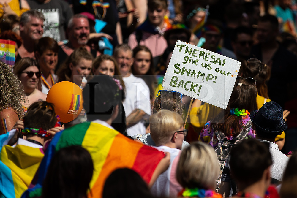 "© Licensed to London News Pictures . 05/08/2018. Leeds, UK. "" Theresa give us our swamp back "" placard in reference to British Prime Minister Theresa May . Leeds Gay Pride parade through the Yorkshire city's centre . Leeds's annual Gay Pride festiva celebrates the city's LGBTQ+ life and culture . Photo credit: Joel Goodman/LNP"