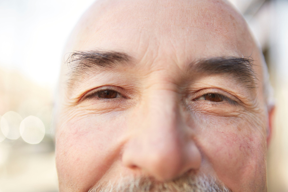 Close up smiling eyes portrait photograph of bald man in 50s with white mustache