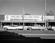 """0301-899A. T. E. Coxwell. Pancho's. Santa Fe Restaurant,"""" 274 East Wickenburg Way, now the Gold Nugget Restaurant. (Tucker E. Coxwell was owner of Pancho's. In these photos, the Santa Fe Cafe is vacant and has a for lease sign in the door. Cars have 1957 license plates. In the window is a """"Re-elect Lew Bramkamp"""" sign. Lewis Bramkamp was a state representative and lived in Wickenburg. Coxwell moved Pancho's to a new location in 1957, which could be this restaurant)"""