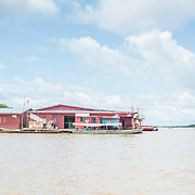 CAPTION: As the boat approaches the harbour at Benjamin Constant, a floating dentist can be seen in the river. These outposts operate like a country within a country. Brazil's central authorities have instituted a specific department to take care of their needs. LOCATION: Paraná Benjamin Constant, Rio Javari, Amazonas, Brazil. INDIVIDUAL(S) PHOTOGRAPHED: N/A.
