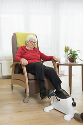 Senior woman doing exercise on mini foot pedal exerciser in rest home