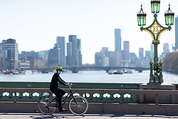© Licensed to London News Pictures. 23/03/2020. LONDON, UK. A woman cycles across a quiet Westminster Bridge this afternoon. The government has advised people to practice social distancing measures that help reduce the transmission of Coronavirus (COVID-19). Photo credit: Luke Dray/LNP
