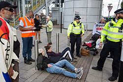 London, UK. 4 September, 2019. Metropolitan Police officers monitor anti-nuclear activists locked together using an arm tube within a shopping basket who they had dragged out of one of the two main access roads to ExCel London during protests on the third day of a week-long carnival of resistance against DSEI, the world's largest arms fair. The third day's protests were organised by the Campaign for Nuclear Disarmament (CND) and Trident Ploughshares.