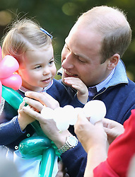File photo dated 29/09/16 of Princess Charlotte being held by the Duke of Cambridge at a children's party for military families at Government House in Victoria during the Royal Tour of Canada. The Duke and Duchess of Cambridge will celebrate their daughter Princess Charlotte's second birthday on Tuesday.