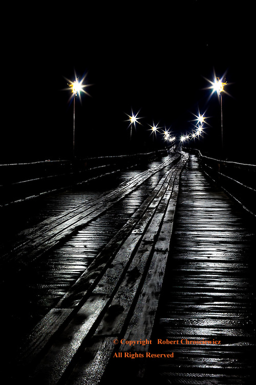 Morning Bridge: Morning's heavy fog engulfs the wooden Saphan Mon Bridge, leaving it gleaming in the heavy dew while incandescent lanterns light the way into the darkness, Sangkhlaburi Thailand.