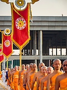 """11 FEBRUARY 2016 - KHLONG LUANG, PATHUM THANI, THAILAND: Buddhist monks walk into the pagoda during the Makha Bucha Day service at Wat Phra Dhammakaya.  Makha Bucha Day is a public holiday in Cambodia, Laos, Myanmar and Thailand. Many people go to the temple to perform merit-making activities on Makha Bucha Day, which marks four important events in Buddhism: 1,250 disciples came to see the Buddha without being summoned, all of them were Arhantas, or Enlightened Ones, and all were ordained by the Buddha himself. The Buddha gave those Arhantas the principles of Buddhism. In Thailand, this teaching has been dubbed the """"Heart of Buddhism."""" Wat Phra Dhammakaya is the center of the Dhammakaya Movement, a Buddhist sect founded in the 1970s and led by Phra Dhammachayo. Makha Bucha Day is one of the most important holy days on the Thai Buddhist calender.      PHOTO BY JACK KURTZ"""