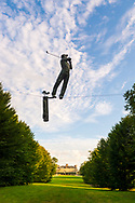 """Old Westbury, New York, U.S., September 1, 2019. """"Golfer"""" is one of 33 outdoor sculptures by Jerzy Kedziora (Jotka), b. 1947 in Poland, and his Balance in Nature art is on view at historic Old Westbury Gardens in Long Island, until October 20, 2019. The life-size, bronze resin balancing sculpture is on a wire suspended high between trees, and is swinging a golf club. Far in background is mansion undergoing restoration"""