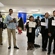 Protesters against a possible third runway at Heathrow and aviation in general for contributing to climate change line up in arrivals with messages for travelers at terminal 3 at Heathrow, London, Oct 1st 2016.