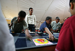 03 Feb 2006. East New Orleans, Louisiana.<br /> Tet, or Tet Nguyen Dan, Vietnamese Lunar New Year. Year of the Dog celebrations amongst the Vietnamese community of East Orleans. Gamblers exchange cash and smiles playing Bau Cua amidst furious scenes in a mini Vietnamese 'casino' where proceeds allegedly go to the church to aid in the rebuilding of the area and the creation of an elderly retirement home in the community.<br /> Photo; Charlie Varley/varleypix.com