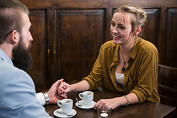 Young couple holding hands while sitting at cafÈ