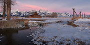 Alpenglow light over the Grand Teton mountain range with the historic Moulton Barn and fence line.
