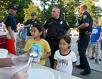 Catherine and Christine Pingol are served a blue Italian Ice at Laconia's National Night Out event at Woodland Heights School Tuesday evening.  In the background are Laconia Commissioner Armand Maheux, Officer Kevin Shortt and Chief Chris Adams.   (Karen Bobotas/for the Laconia Daily Sun)