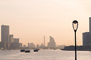 View of the modern skyline of Pudong under a moody sky at sunrise and barges on the Huangpu river, Shanghai, China