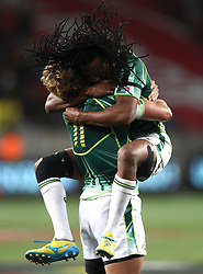 Werner Kok of South Africa and Cecil Afrika of South Africa  celebrate after South Africa beat New Zealand to win the Cup Final during the Cup Final match between South Africa and New Zealand on Day 2 of the HSBC Sevens World Series Port Elizabeth Leg held at the Nelson Mandela Bay Stadium on 8th December 2013 in Port Elizabeth, South Africa. Photo by Shaun Roy/Sportzpics