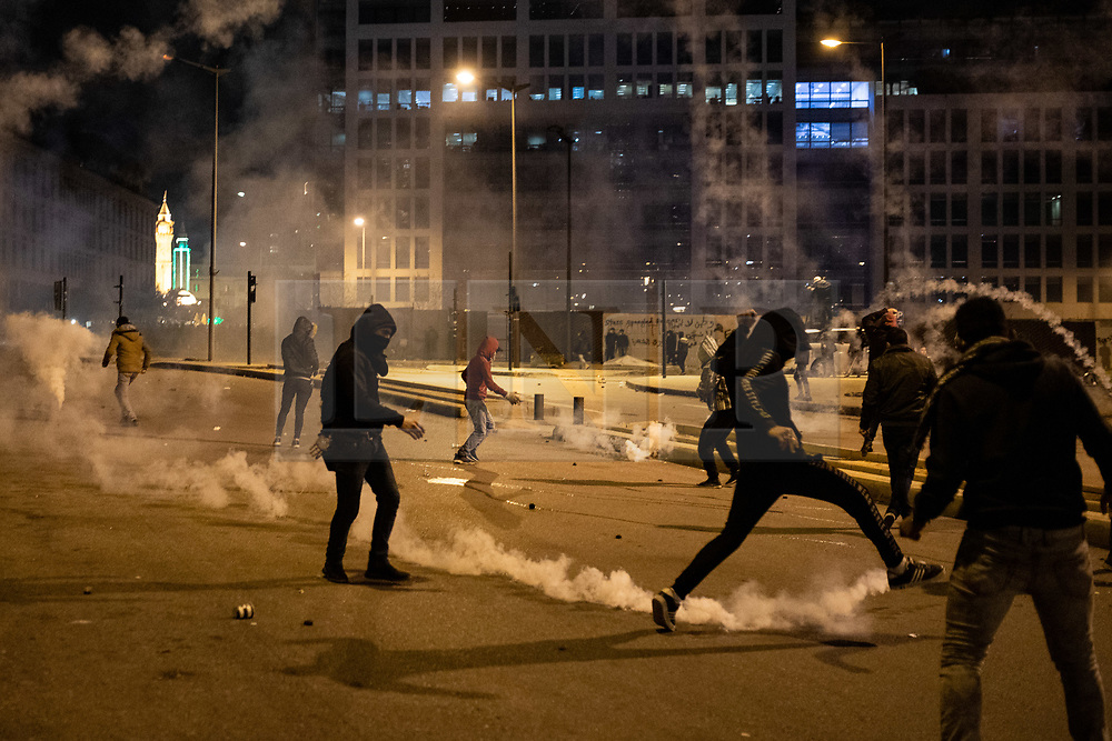 """© Licensed to London News Pictures. 22/01/2020. Beirut, Lebanon. Demonstrators throw tear gas canisters back to police on Martyrs' Square, Beirut, during a riot following the announcement late last night that a government has been formed. Police respond with tear gas and water cannon against the anti-government demonstrators. Violence has been escalating in the capital following a """"week of wrath"""", where demonstrators were campaigning against government corruption and economic crisis. Photo credit : Tom Nicholson/LNP"""