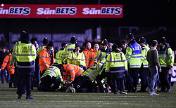 Fans on the pitch are dealt with by police and stewards after the game