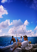 Two men are sport fishing off a boat in the carribean waters of the British Virgin Islands