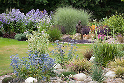 Looking towards statue 'Boy on the Rock' by Jane Hogben. Foreground planting of Eryngium x oliverianum and Eryngium agavifolium