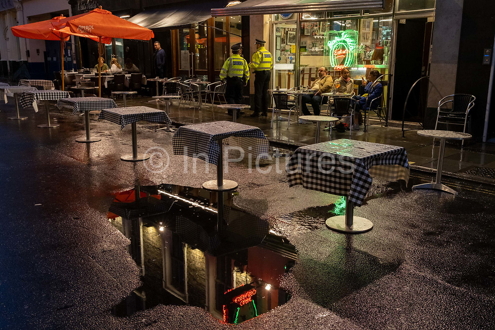 On a rainy night in Soho, Met police officers make a presence outside Bar Italia on Frith Street at a time when recently re-opened bars and restaurants are desperate for customer business during the coronavirus pandemic, on 27th August 2020, in London, England.