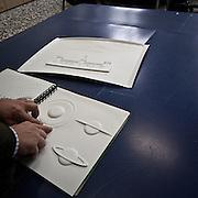 Produzione di pannelli di resina nel laboratorio dell'Istituto dei Ciechi a Milano, seguendo i criteri dell'alfabeto Braille. Con questi pannelli i ciechi possono leggere e conoscere i monumenti attraverso il tatto..Due figure a confronto: Saturno con l'anello riprodotto in tre angolazioni diverse, per far comprendere che attorno al pianeta  ruota un anello cavo; e il Castello Sforzesco. La differenza più evidente è la differente quantità di particolari. ..Production of resin panels in the laboratory of the Institute of the Blind people to Milan, following the criteria of the Braille alphabet. With these panels the blind people can read and know monuments through the tact..Two figures to comparison: Saturno with the reproduced ring in three various angles-shot, in order to make to comprise that around the planet orbit an empty ring; and the Castello Sforzesco. The most obvious difference is the different amount of detail.