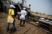 A health worker and a community volunteer got on board a ferry at the ferry terminal in Makango, northern Ghana, to find children to vaccinate during a national polio immunization exercise on Thursday March 26, 2009.