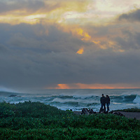 A couple walks by the Pacific Ocean in Fort Bragg, California.