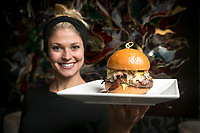 Jessica Heidenreich holds the Firehouse burger which comes with spicy bacon, habanero jack cheese, giardiniera, tomato and avocado mayonaise at Eden in Glendale, CA. May 24, 2013.  Photo by David Sprague ©2013