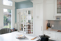 A transitional style white kitchen is newly installed in a Victorian home built in the early 1920s, and features white custom millwork by Thomas Philips Woodworking, a large marble island with a conduction cooktop and a rose-colored glass cabinet.