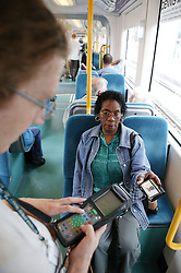 Woman showing her travel pass to the tram conductor,
