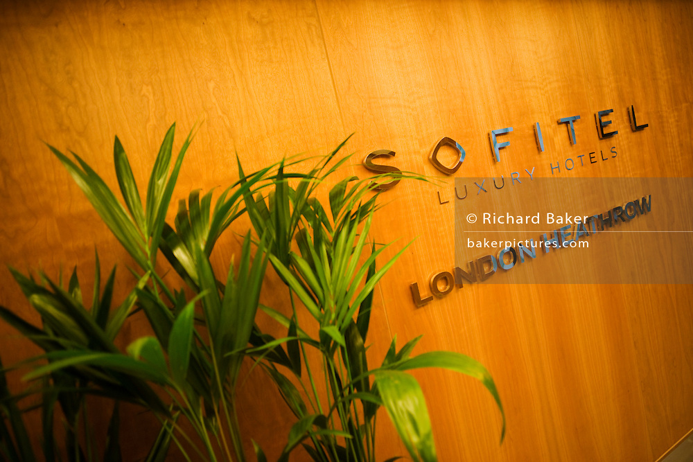 Sofitel entrance with potted plant and branding on wall at Heathrow's terminal 5 hotel.