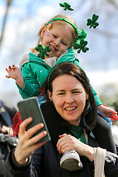 © Licensed to London News Pictures. 17/03/2019. London, UK. A woman takes a selfie during the St Patrick's Day parade as it travels through the streets of central London. Photo credit: Dinendra Haria/LNP