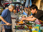 "13 MARCH 2016 - LUANG PRABANG, LAOS: A market vendor sells Lao curries to an elderly shopper in the market in Luang Prabang. Luang Prabang was named a UNESCO World Heritage Site in 1995. The move saved the city's colonial architecture but the explosion of mass tourism has taken a toll on the city's soul. According to one recent study, a small plot of land that sold for $8,000 three years ago now goes for $120,000. Many longtime residents are selling their homes and moving to small developments around the city. The old homes are then converted to guesthouses, restaurants and spas. The city is famous for the morning ""tak bat,"" or monks' morning alms rounds. Every morning hundreds of Buddhist monks come out before dawn and walk in a silent procession through the city accepting alms from residents. Now, most of the people presenting alms to the monks are tourists, since so many Lao people have moved outside of the city center. About 50,000 people are thought to live in the Luang Prabang area, the city received more than 530,000 tourists in 2014.    PHOTO BY JACK KURTZ"