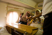 Dr Safaa Elagib Adam and Maha Faraigon help themselves to airline sweets near the window on a flight to attend the first-ever international Conference on Womens' Challenge in Darfur. Discussing conference matters, they sit in a chartered Russian Antonov aircraft during flight to Al Fasher (also spelled, Al-Fashir) in north Darfur where women from remote parts of Sudan gathered to discuss peace and political issues. The short flight saves them a hazardous five-day drive by road, known for extreme acts of violence by rebels and Janjaweed soldiers.