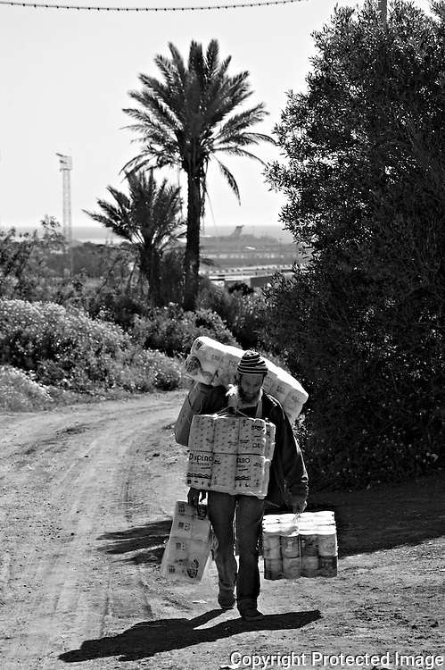 MELILLA, SPAIN - APRIL 19, 2010 : Women carrying  contraband goods up to 80 kg. in weight  to pass through Morocco in the border of  El Barrio Chino on April 19 , 2010 in Melilla. Spain. Every day at the pedestrian border of El Barrio Chino hundreds of people are involved in transporting smuggled goods from Melilla a Spanish enclave on the North African coast to Morocco.For each package introduced in morocco receive between 3 an 5 euros depending on size,with a little luck achieved make three trips a day.It is estimated that from Monday to Thursday on foot enter Melilla 8.000 porters, mostly women, to return to Morocco with huge sacks of goods from the warehouse border area of Beni Enzar in Melilla .( Photo by Jordi Cami  )