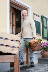 Portrait of a mature man holding basket full of vegetables in wholefood shop and smiling, Bavaria, Germany