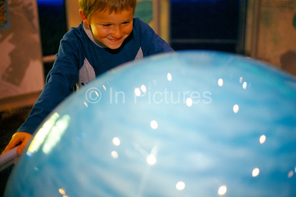 A boy looking at an exhibit of the Solar System at the National Space Centre, Leicester, UK.