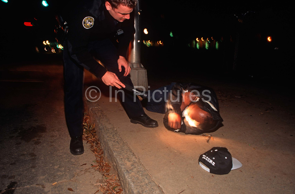 During his night patrol, a 1990s Atlanta Police Officer shines his torchlight into the face of a man lying on the ground, on 5th November 1995, in Atlanta, Georgia USA.