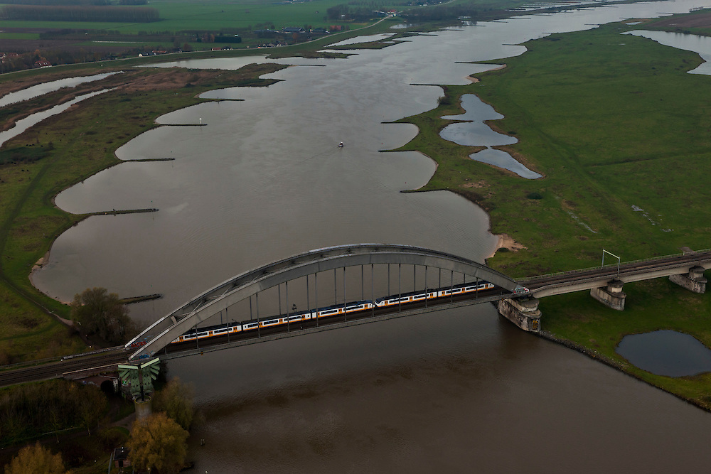 Nederland, Gelderland, Culemborg, 15-11-2010. Rivier de Lek en spoorbrug Culemborg (Kuilenburgse spoorbrug). In de Goilberdingerwaard en Baarsemwaard (links) is de zomerdijk verlaagd  en gedeeltelijk weggegraven en ook zijn in de uiterwaard geulen gegraven om rivier de Lek bij hoogwater meer de ruimte te geven. Natuurontwikkelingsproject.Railway bridge Culemborg and Lek River. In the floodplains (left) the summer dike has been reduced in height and partially excavated, and trenches haven been dug to create 'room for the river' at heigh waters. Nature Project.luchtfoto (toeslag), aerial photo (additional fee required).foto/photo Siebe Swart