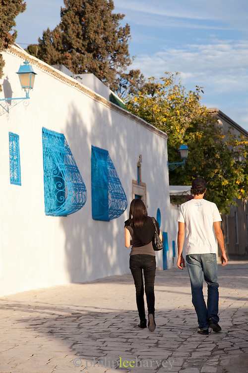 Young couple walking along street, Sidi Bou Said, Tunisia