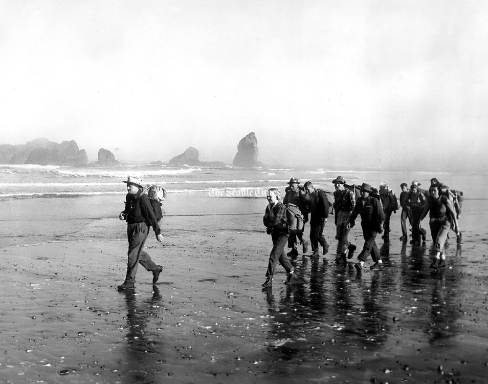 Offshore pinnacles and rocks appeared out of the morning fog as Justice William O. Douglas led hikers along the beach on their way from Lake Ozette to Rialto Beach, near La Push. Their purpose was to dramatize a protest against a proposed coastal highway, which would reduce the already small number of natural coastline miles in the United States. (The Seattle Times, 1958)