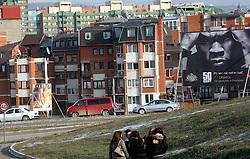 PRISTINA, KOSOVO - DECEMBER 14 - mladina, dekleta se objemajo, v ozadju reklama za koncert 50 cent, ki bo v Pristini ob zacetku delovanja mobilnega operaterja IPKA.