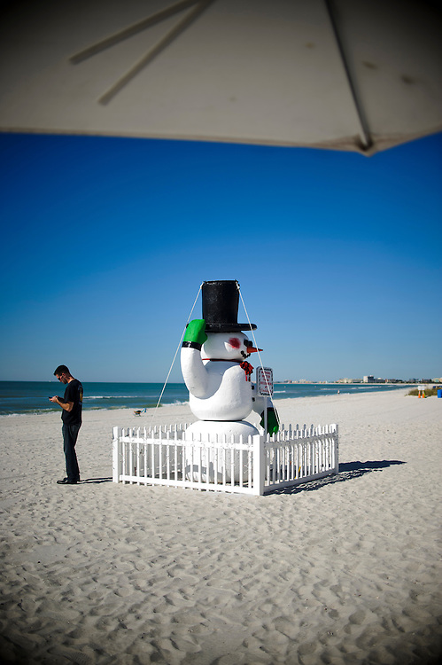 A man on his cell phone seems unfazed by the snow man on Treasure Island Beach in Florida December 18, 2011.<br /> <br /> Photo by Matt Roth