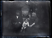 little child with grandparents sitting on a bench circa 1920s
