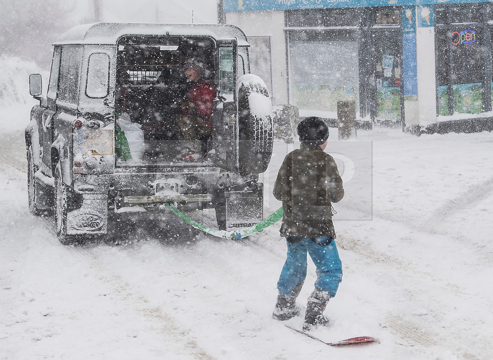 © Licensed to London News Pictures. 28/02/2018. The Lizard, UK.  A young man using a snowboard attached to the back of a 4x4 vehicle as The beast from the east struck The Lizard, the most southerly point of Great Britain, today causing havoc in Cornwall. Photo credit: MARK HEMSWORTH/LNP