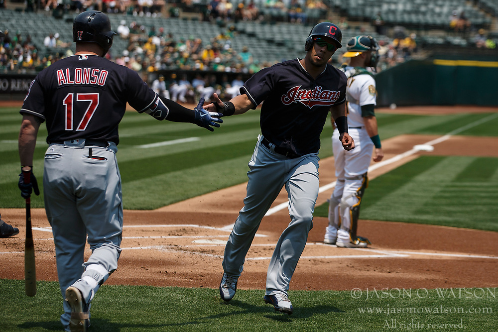 OAKLAND, CA - JULY 01:  Michael Brantley #23 of the Cleveland Indians is congratulated by Yonder Alonso #17 after scoring a run against the Oakland Athletics during the first inning at the Oakland Coliseum on July 1, 2018 in Oakland, California. The Cleveland Indians defeated the Oakland Athletics 15-3. (Photo by Jason O. Watson/Getty Images) *** Local Caption *** Michael Brantley; Yonder Alonso