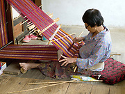 Namgay Pedon weaving naturally dyed wild silk using a traditional back-strap floor loom in Rangjung village, Eastern Bhutan. She is weaving fabric to make a 'kira' the Bhutanese women's traditional floor length dress.