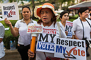 """19 JANUARY 2014 - BANGKOK, THAILAND: Thais gather in Benjasiri Park to pray for peace and support democracy. """"Respect my vote"""" has become a rallying cry of people who are concerned their could be a military coup in Thailand. Hundreds of people came to Benjasiri Park, a few hundred meters from the anti-government protest site in Asok Intersection, Sunday evening to pray for peace and rally for a respect for democracy Sunday. The vigil took place a few hours after a two explosive devices, thought to be grenades, were thrown at the protest site near Victory Monument, several kilometers north of Asok. The grenade attack Sunday was the 2nd daytime grenade attack in three days on anti-government protestors. No arrests have been made in the incidents.    PHOTO BY JACK KURTZ"""
