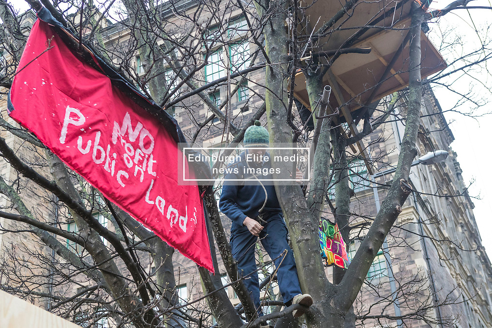 A protestor, Simon Byrom, is camped in the trees above a site in Edinburgh's Old Town destined to be a £65m hotel. The action is part of a campaign called Let There Be Light which uses the quotation which is over the door of Edinburgh Central Library which will be dwarfed by the proposed hotel and prevent any natural light entering the library.