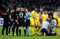 Chelsea's Jorginho (ground, right) and Eintracht Frankfurt's Sebastian Rode are checked over by staff and Referee Carlos Del Cerro after receiving head injuries during the UEFA Europa League Semi final, first leg match at The Frankfurt Stadion, Frankfurt.
